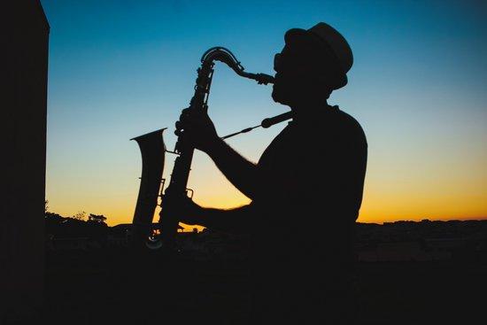 Photo d'un saxophoniste qui joue devant un coucher de soleil.